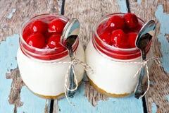 Dois bolos de queijo da cereja em uns frascos de pedreiro em uma madeira rústica Fotos de Stock Royalty Free