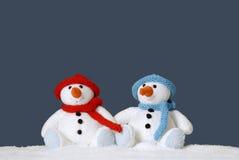 Dois bonecos de neve bonitos que sentam-se na neve Imagens de Stock Royalty Free