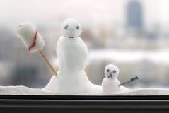 Dois bonecos de neve pequenos atrás de uma janela Fotos de Stock Royalty Free