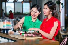 Dois bonitos e jovens mulheres alegres que escolhem queques em uma cafetaria na moda Imagens de Stock