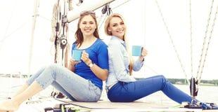 Dois bonitos, felizes e moças que apreciam um bom dia de verão em um iate e que comem um chá fotografia de stock