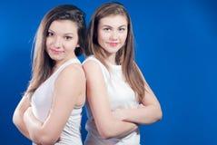 Dois bonitos mulher nova que está de volta à parte traseira Fotografia de Stock Royalty Free