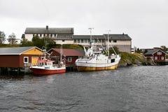 Dois botes no porto de Reine na frente das cabines de pesca de madeira tradicionais em ilhas de Lofoten em Noruega fotografia de stock royalty free