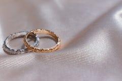 Dois brancos e alianças de casamento douradas cor-de-rosa no fundo do cetim, conceito das alianças de casamento foto de stock royalty free