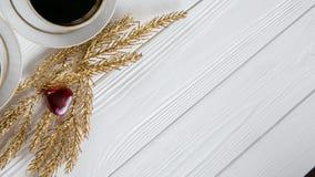 Dois brancos e xícaras de café douradas com ramos dourados decorativos e coração pequeno do vidro e o vermelho no fundo de madeir Fotos de Stock Royalty Free