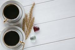 Dois brancos e xícaras de café douradas com ramos dourados decorativos e corações de vidro pequenos no fundo de madeira branco Fotografia de Stock Royalty Free