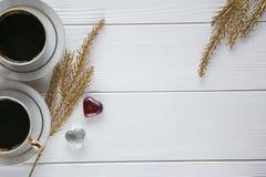 Dois brancos e xícaras de café douradas com ramos dourados decorativos e corações de vidro pequenos no fundo de madeira branco Foto de Stock