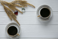 Dois brancos e xícaras de café douradas com ramos dourados decorativos e corações de vidro pequenos no fundo de madeira branco Fotos de Stock