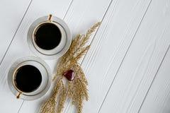 Dois brancos e xícaras de café douradas com ramos dourados decorativos e corações de vidro pequenos no fundo de madeira branco Imagens de Stock Royalty Free