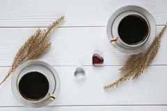 Dois brancos e xícaras de café douradas com ramos dourados decorativos e corações de vidro pequenos no fundo de madeira branco Fotos de Stock Royalty Free