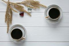 Dois brancos e xícaras de café douradas com ramos dourados decorativos e corações de vidro pequenos no fundo de madeira branco Imagem de Stock