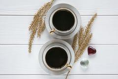 Dois brancos e xícaras de café douradas com ramos dourados decorativos e corações de vidro pequenos no fundo de madeira branco Fotografia de Stock