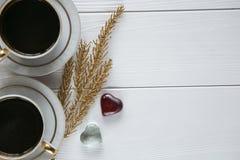 Dois brancos e xícaras de café douradas com ramos dourados decorativos e de vidro pequeno e dois corações no fundo de madeira bra Foto de Stock