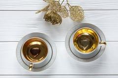 Dois brancos e xícaras de café douradas com ramos dourados decorativos e dois corações no fundo de madeira branco Imagens de Stock