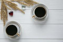 Dois brancos e xícaras de café douradas com ramos dourados decorativos e dois corações no fundo de madeira branco Imagens de Stock Royalty Free