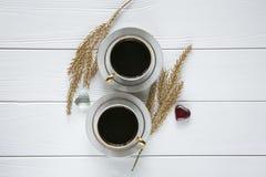 Dois brancos e xícaras de café douradas com ramos dourados decorativos e vidro pequeno, dois corações no fundo de madeira branco Fotografia de Stock Royalty Free