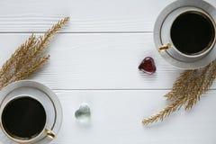 Dois brancos e xícaras de café douradas com ramos dourados decorativos no fundo de madeira branco Fotos de Stock