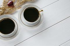 Dois brancos e xícaras de café douradas com ramos dourados decorativos no fundo de madeira branco Fotografia de Stock