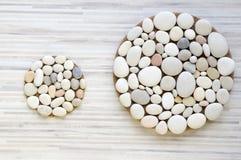 Dois círculos mágicos da pedra dão forma no fundo branco e cinza descascado, seixos claros, mandalas feitas das pedras imagens de stock