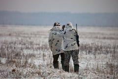 Dois caçadores na camuflagem do inverno à espreitadela acima no campo imagem de stock