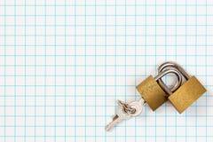 Dois cadeado ligados que encontram-se no papel quadrado Imagem de Stock