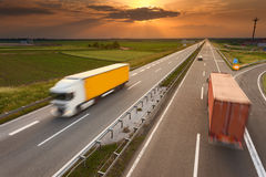 Dois caminhões no borrão de movimento na estrada no por do sol Fotos de Stock Royalty Free