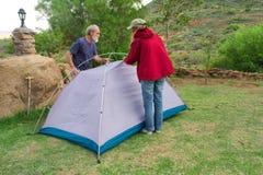 Dois caminhantes montam barracas no local de acampamento Imagens de Stock Royalty Free