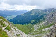 Dois caminhantes que descem em um vale nos moutains em um dia nebuloso, Áustria de Allgaeu Foto de Stock