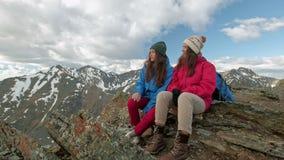 Dois caminhantes que relaxam sobre o monte e que apreciam o nascer do sol sobre o vale vídeos de arquivo