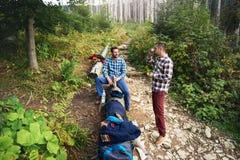 Dois caminhantes que tomam uma ruptura de trekking na floresta imagem de stock royalty free