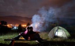 Dois campistas que sentam-se de volta à barraca e à fogueira próximas traseiras foto de stock