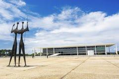 Dois Candangos monument och Planalto slottbyggnad i Brasilia, Brasilien Fotografering för Bildbyråer