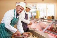 Dois carniceiros que preparam a carne na loja Foto de Stock