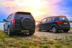 dois carros na costa do lago Fotografia de Stock