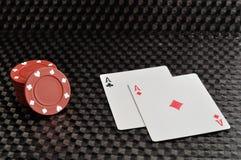Dois cartões e microplaquetas de pôquer vermelhas em um fundo preto Fotos de Stock