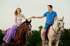 Dois cavaleiros a cavalo no por do sol na praia Hors do passeio dos amantes Imagem de Stock