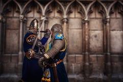 Dois cavaleiros que lutam a catedral medieval do agaist imagem de stock