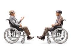 Dois cavalheiros idosos nas cadeiras de rodas que têm uma conversação fotos de stock royalty free