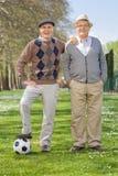 Dois cavalheiros superiores que levantam com um futebol fotos de stock royalty free