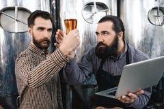 Dois cervejeiros farpados verificam a qualidade da cerveja na cervejaria Experiência da qualidade da cerveja Controle da qualidad imagens de stock