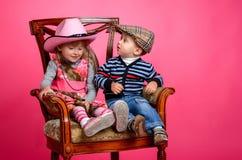 Dois chapéus de vaqueiro vestindo de sorriso das crianças fotografia de stock royalty free