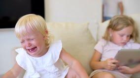 Dois childs que olham o ANG usando a tabuleta em casa Crianças que usam um laplop moderno, tabuleta no sofá discussão das irmãs s video estoque