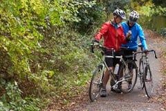Dois ciclistas masculinos maduros no passeio que olha o telefone celular App Imagens de Stock Royalty Free