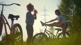 Dois ciclistas, uma menina aquecem-se, os outro bebem a água e o descanso antes de dar um ciclo vídeos de arquivo