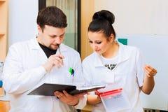 Dois cientistas com jornal do laboratório Fotografia de Stock Royalty Free