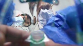 Dois cirurgiões que olham outro um paciente quando um puser a máscara com anestesia outro o paciente vídeos de arquivo