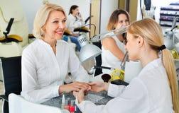 Dois clientes das mulheres que têm o tratamento de mãos feito no salão de beleza do prego Foto de Stock