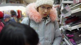 Dois clientes fêmeas escolhem acessórios da cozinha na loja de ferragens filme