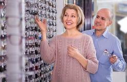 Dois clientes maduros na loja dos vidros fotografia de stock
