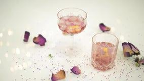 Dois cocktail com as pétalas do limão e da flor na tabela branca com reflexão piscar filme